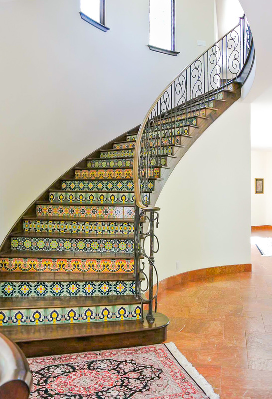Mediterranean style tiled staircase with wrought iron hand rails separates the first and second floors of the Saratoga home designed by Golden Visions Design